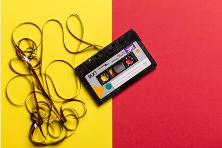 Thumb black cassette tape on top of red and yellow surface 1626481